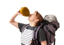 A Girl In A Gray T-shirt With A Large Hiking Backpack Drinks From A Flask On A White Background. The Concept Of Hiking, Traveling, Thirst