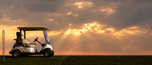 Golf cart park on green grass at golf course with sun light ray form black cloud.
