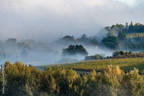 Fototapeta premium Magical outline of a misty valley in the morning landscape, the countryside of Tuscany, Italy, Europe