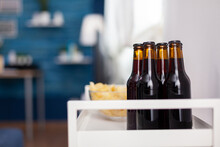 Close Up Of Dark Beer Bottle In Elegant Apartment. Modern Living Room With Nobody In With Blue Furniture And Walls, Beautiful Decorated. Pretty Simple Decor Of Apartment. Elegant Retro Decoration