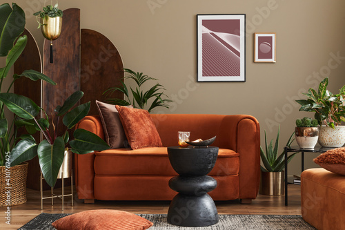 Fototapeta Domestic interior of living room with design sofa, mock up poster frames, a lot of plants, coffee table, room screen and elegant personal accessoreis in modern home decor. Template. obraz