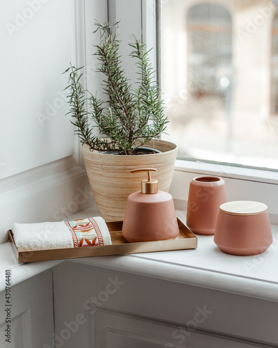 Fotografie, Obraz Vertical shot of rosemary plant and ceramic bathroom accessory set with a towel