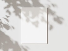 Empty White Vertical Rectangle Poster Mockup With Soft Hawthorn Leaves Shadows On Neutral Light Grey Concrete Wall Background. Flat Lay, Top View 3D Illustration