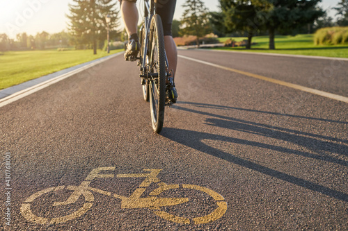 Place to train. Close up of a bicycle sign drawn on asphalt. Professional male cyclist riding a road bike on a cycle path - fototapety na wymiar