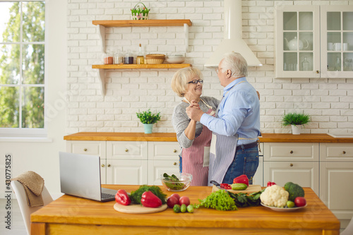 Fototapeta Happy loving mature couple having fun and dancing waltz while cooking healthy vegetarian meal in modern Scandinavian kitchen at home