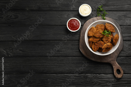 Obraz Cooked soy meat in bowl on black wooden table, flat lay. Space for text - fototapety do salonu