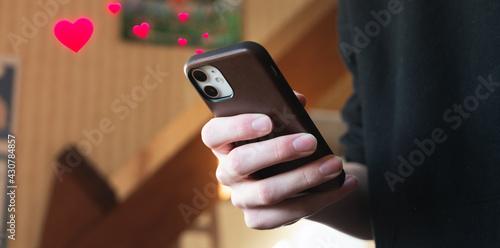 Obraz na plátně Jeune homme mettant des J'aime (likes sous forme de cœurs) sur son téléphone por