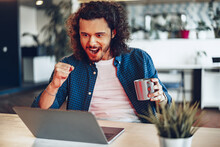 Excited Overjoyed Young Businessman Looking At Laptop Screen Happy To Win Or Recieved Good News