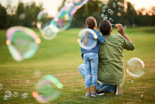 Rear View Of Young Father And His Cute Little Girl Having Fun While Blowing Soap Bubbles In The Park, Daughter And Dad Spending Time Together Outdoors