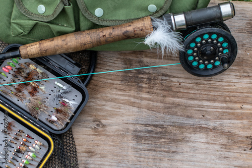 Fototapeta fly fishing equipment on a old wooden board background, negative space