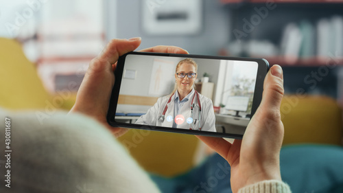 Fototapeta Close Up of a Female Chatting in a Video Call with Her Female Family Doctor on Smartphone from Living Room. Ill-Feeling Woman Making a Call from Home with Physician Over the Internet. Horisontal Vew. obraz