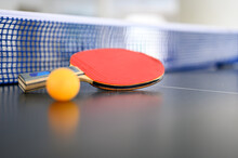 Red Racquet With Orange Table Tennis Ball Put On The Table With Blue Net For Ready To Play Ping Pong.
