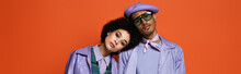 Curly Woman In Purple Jacket Leaning On Model In Beret And Sunglasses Isolated On Orange, Banner