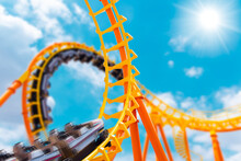 Most Exciting Roller Coaster Drive High To Summer Sky At Theme Park, People Excited Fun And Joyful Playing Machine In Holiday.