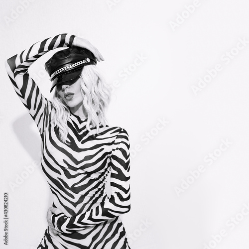 Photo Sensual sexy androgenic model in freak stylish zebra print clothes and leather trendy black cap posing in a white studio