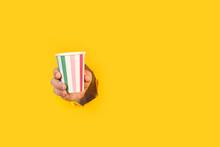 Mano De Hombre Sosteniendo Un Vaso A Rayas De Colores Desechable A Través De Un Agujero De Una Pared De Color Amarillo Liso Y Aislado. Vista De Frente Y De Cerca. Copy Space