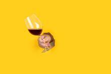 Mano De Un Hombre Que Emerge A Través De Un Agujero Rasgado En Un Papel Amarillo Con Una Copa De Vino Tinto.  Vista De Frente. Copy Space