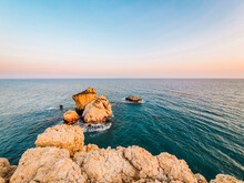 Sea At Sunset, White Rocks Lit By The Setting Sun, Calm Waters, Pink-red Horizon. Relaxing Paradise