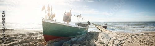Fotografie, Obraz Old green fishing boat standing on land in a small village, sandy shore (sand dunes) of the Baltic sea, Latvia
