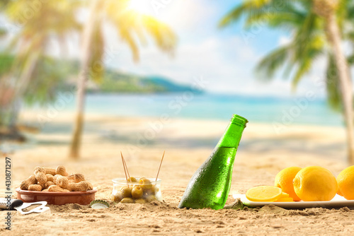 Beer buried in sand with aperitif on a beach - fototapety na wymiar