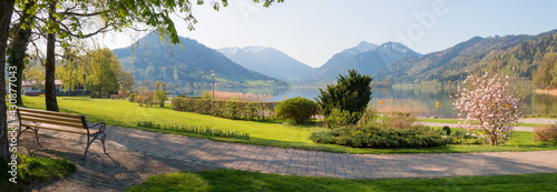 Canvas spa garden Schliersee with bench and lake view, bavarian landscape at springtime