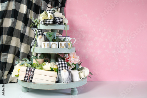 Photo On-trend Farmhouse aesthetic three tiered tray decor filled with white pumpkins, cute black plaid gnomes, and farmhouse style stack of books mockup