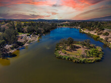 A Stunning Aerial Shot Of The Vast Green And Blue Lake Water With Lush Green And Yellow Plants On The Hillside With Miles Of Homes And Lush Green Trees And Clouds At Laguna Niguel Regional Park