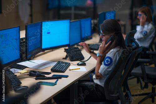 Fototapeta Security guard monitoring modern CCTV cameras in a surveillance room