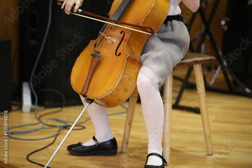 Foto A little girl plays the cello with a bow