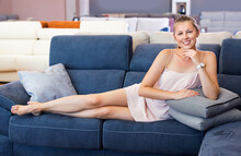 Cheerful Positive Woman Buyer Lying Barefoot With Pillow On The Sofa In Furniture Shop