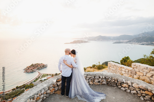 The bride and groom are embracing on the observation deck overlooking the island Wallpaper Mural