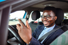 Man Sitting In Car With Mobile Phone In Hand Texting While Driving. Distracted Shocked Guy Checking His Smart Phone Not Paying Attention At Road Annoyed By Bad Text Message Email Outdoors Background