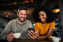 Mixed Race Couple Giggling At Pictures On Social Media Holding Smartphone In Trendy Cafe Shop
