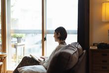 リビングで読書する日本人女性