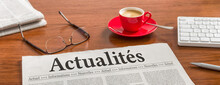 A Newspaper On A Wooden Desk - News In French - Actualités