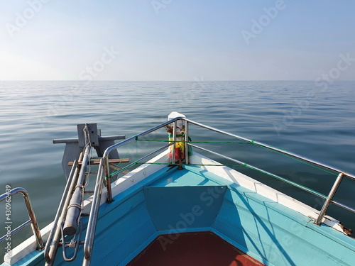 Photo A photograph in the prow of a small blue fishing boat slowly sailing through the sea