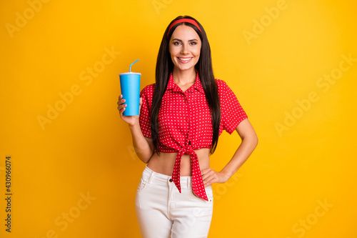 Fototapeta Photo of charming pretty young girl dressed red shirt holding blue soda glass isolated yellow color background obraz
