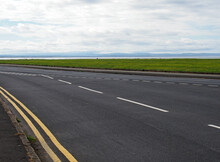 The Coast Road At Crosby In Merseyside With Grass Surrounding The Sea At The Mouth Of The River Mersey