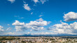 Image of a day with the blue sky and some white clouds. At the base of the image is a city and mountains in the background.