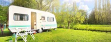 White Caravan Trailer On A Green Lawn In A Camping Site. Sunny Day. Spring Landscape. Europe. Lifestyle, Travel, Ecotourism, Road Trip, Journey, Vacations, Recreation, Transportation, RV, Motorhome