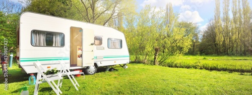 Canvas Print White caravan trailer on a green lawn in a camping site