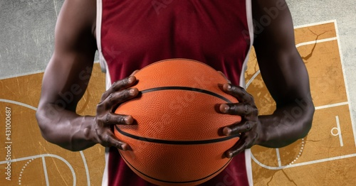 Composition of basketball player holding basketball over basketball court cracked distressed surface