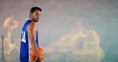 Composition of basketball player holding basketball over flames