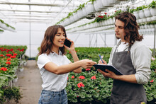 Handsome Male Gardener Holding Clipboard With Woman,which Talking On Phone In Greenhouse.