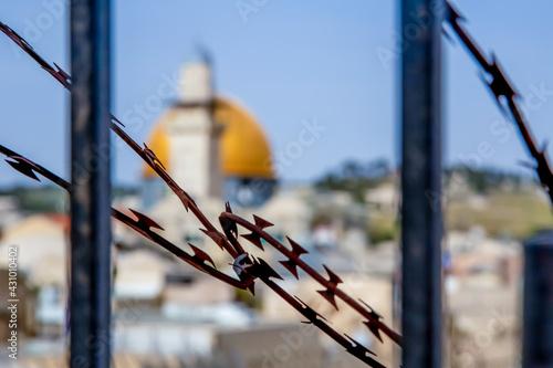 Obraz na płótnie Jerusalem, Israel - 21 april 2021: minaret and dome of rock through barbed wire