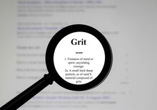 Selective Focus On Word Grit, Word In A Dictionary. Close Up Of An English Dictionary Page With The Word Grit