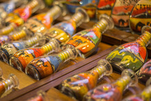 Sand Bottle Souvenirs At The Madinat Jumeirah Souk, Dubai, UAE. Decorative Glass Bottles With Colored Sand Inside Making Shapes Of Desert And Camels