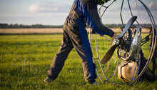 The Pilot Is Preparing A Paralet With A Gasoline Engine For Flights. The Man Starts The Engine. Paragliding For Individual Paragliding Flights. Wing Flight Preparation. Extreme Sports.