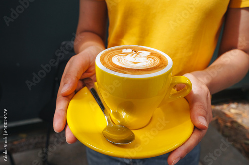 Tela Woman holding  hot cappuccino Yellow coffee cup with heart shape latte art at caff food and drink concept
