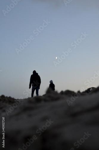 Obraz Ludzie o wschodzie księżyca na plaży - fototapety do salonu
